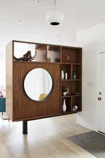To break up the long living room, Pettit created a walnut bookcase near the entrance.