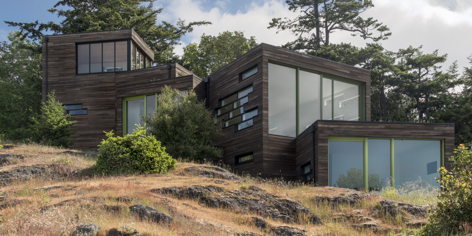 Exterior, Flat RoofLine, House Building Type, Wood Siding Material, and Glass Siding Material  Photo 1 of 6 in A Dramatic Home on San Juan Island Appears to Cascade Toward the Sea