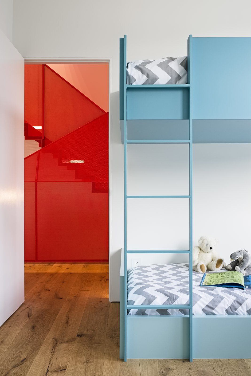 The daughter's bedroom occupies the bay-windowed space that was once the living room. The custom bunkbed, painted in Spring Rain by Benjamin Moore, is by Myers Cabinetry. Dermot Barry was  the project's general contractor and architect Paul Endres  was the structural engineer. Tagged: Kids Room, Bunks, Bedroom, and Light Hardwood Floor.  Photo 8 of 16 in After a Renovation, a Classic San Francisco Victorian Is Now Bursting With Light and Color