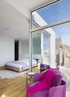 Set on the home's top floor and featuring a deck that overlooks the backyard, the master bedroom is clean-lined and filled with light.. The Fusion bed is by Zeitraum; the purple Cove chairs are by Paola Lenti.