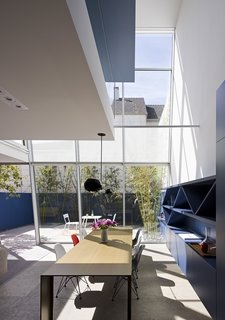 "Transforming the rear of the house is something more often found in a high-rise building—a curtain wall that Fougeron and the team hung from the third floor. ""It's actually very complicated to make the field glazing look simple and minimal,"" says the architect. Piero Lissoni's Metallico table for Porro anchors the dining area, while built-in cabinetry offers ample storage. The main living area was created from what was once a basement behind the garage. Limestone floors inside and out unify the living spaces."