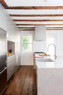 The 12-foot kitchen island, topped in polished Carrara marble, has a waterfall edge and an integrated apron sink made from the same stone slab.