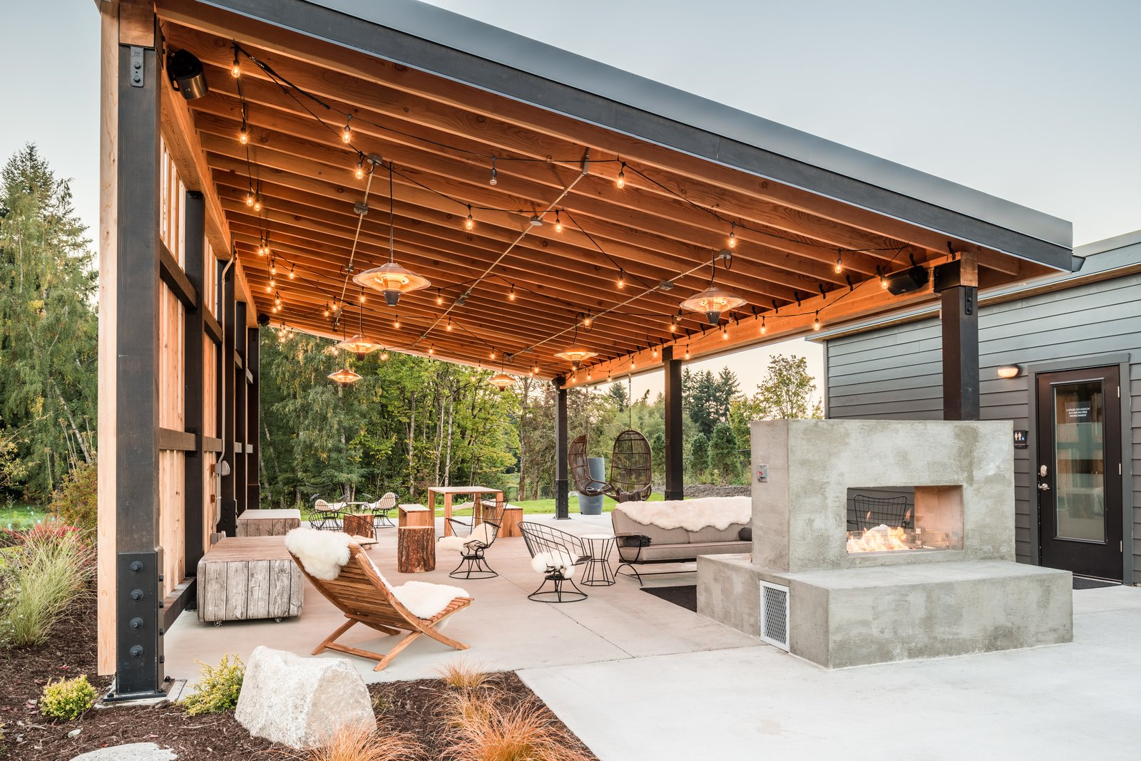 Outdoor, Concrete Patio, Porch, Deck, Back Yard, Shrubs, Trees, Large Patio, Porch, Deck, Hanging Lighting, and Grass The Pavilion has plenty of cozy seating, a cast concrete fireplace, and a sound system.  Photo 5 of 7 in Serenity Awaits at These Prefab Cabin Rentals on Vashon Island