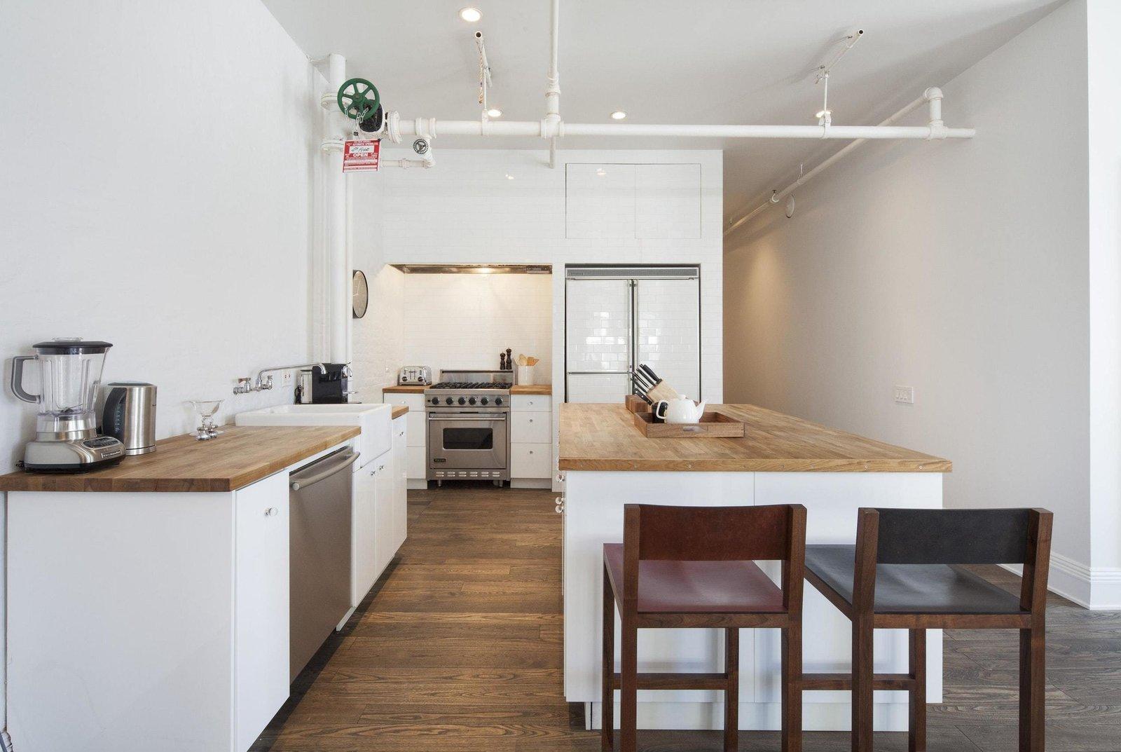 Kitchen, Wood Counter, Wall Oven, Dishwasher, Refrigerator, Range, Medium Hardwood Floor, Vessel Sink, White Cabinet, and Recessed Lighting  Prince Street
