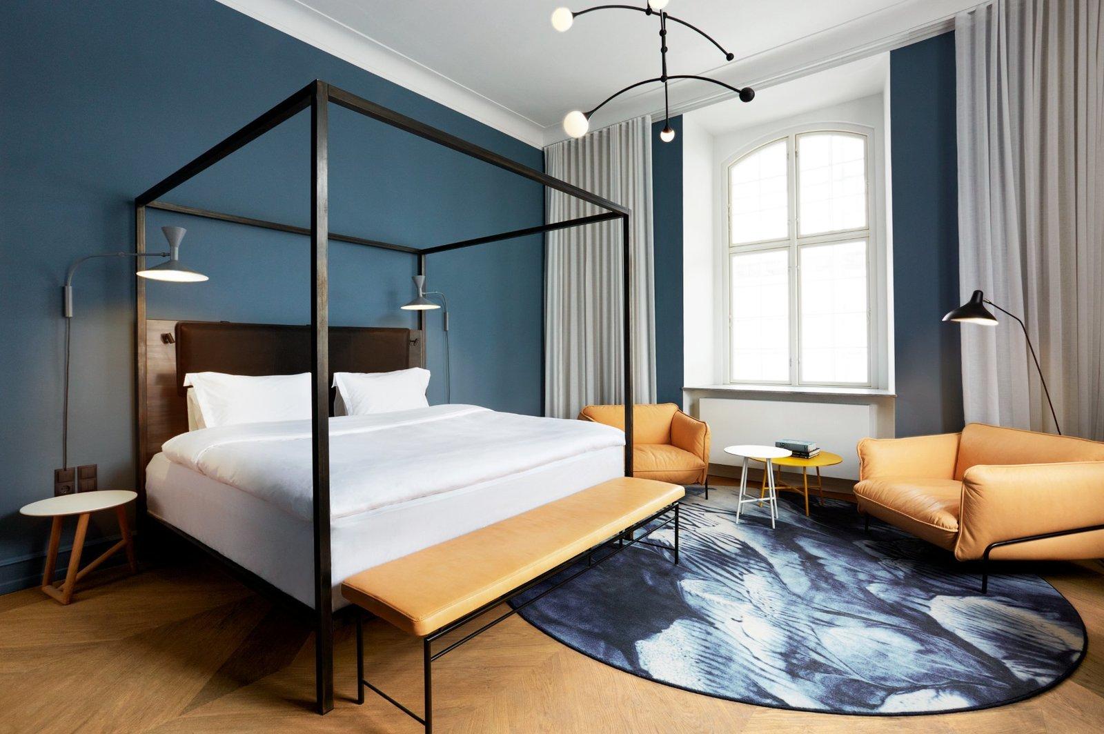 Bedroom, Wall Lighting, Floor Lighting, Chair, Bench, Pendant Lighting, Rug Floor, Night Stands, Medium Hardwood Floor, and Bed  Nobis Hotel Copenhagen