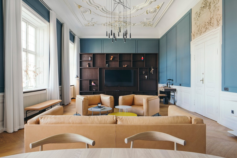 Living Room, Table, Chair, Sofa, Coffee Tables, Media Cabinet, Pendant Lighting, Bench, Rug Floor, and Medium Hardwood Floor  Nobis Hotel Copenhagen
