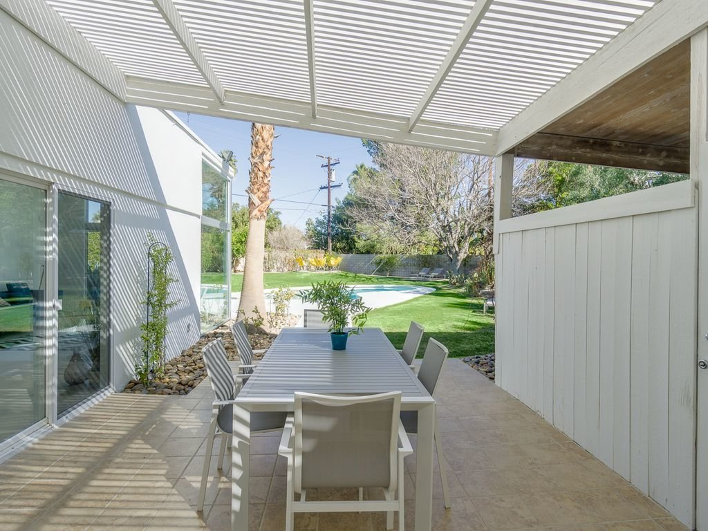 Outdoor, Side Yard, Back Yard, Grass, Small Patio, Porch, Deck, Trees, and Hardscapes  Racquet Club North House With a Citrus-Colored Door
