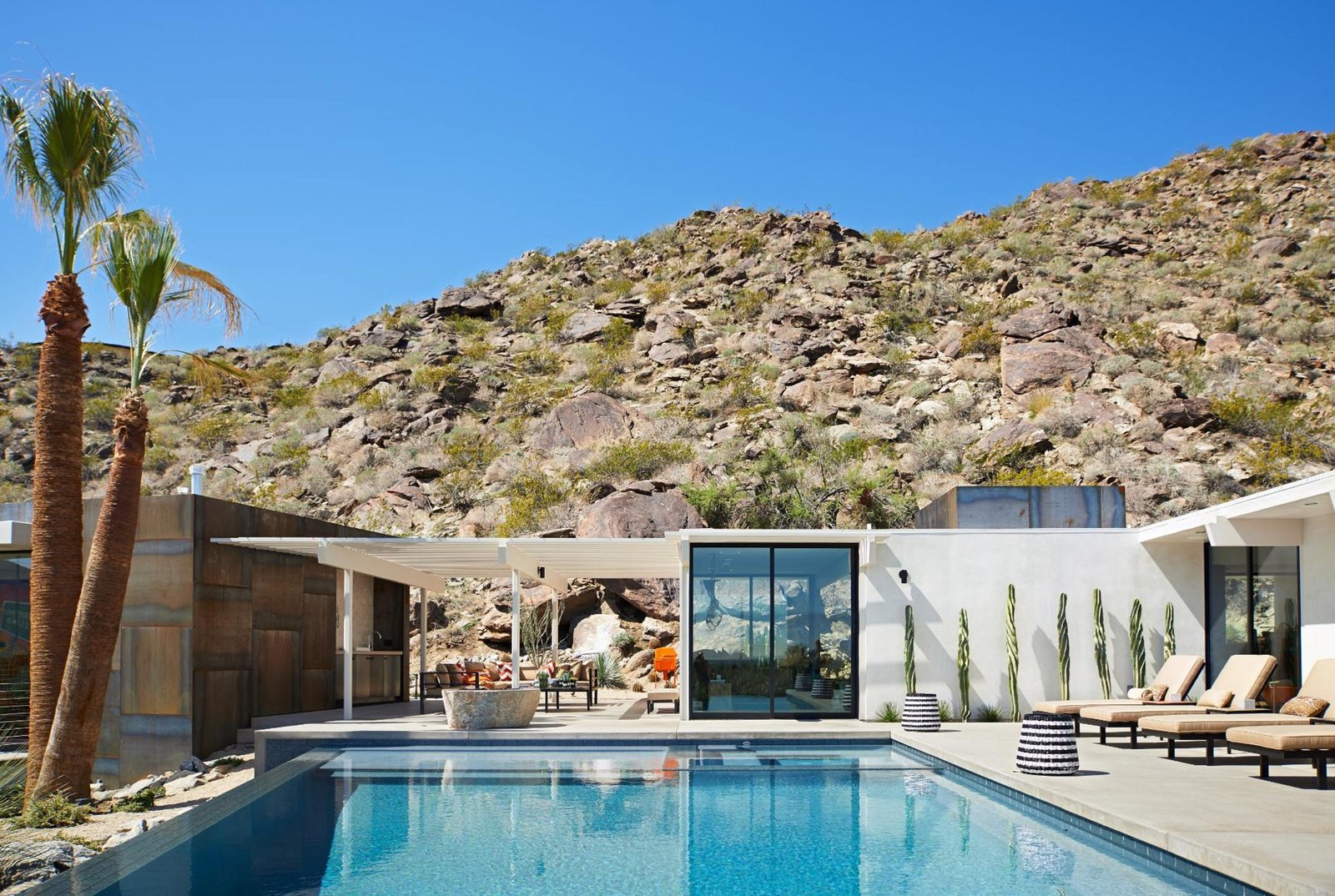Outdoor, Trees, Boulders, Swimming Pools, Tubs, Shower, Concrete Patio, Porch, Deck, Desert, Back Yard, and Salt Water Pools, Tubs, Shower  On the Rocks
