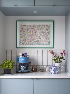 A cerulean espresso machine by Gaggia anchors a kitchen counter tableau. The cabinetry doors are Lastra in Fjord blue by Crown.