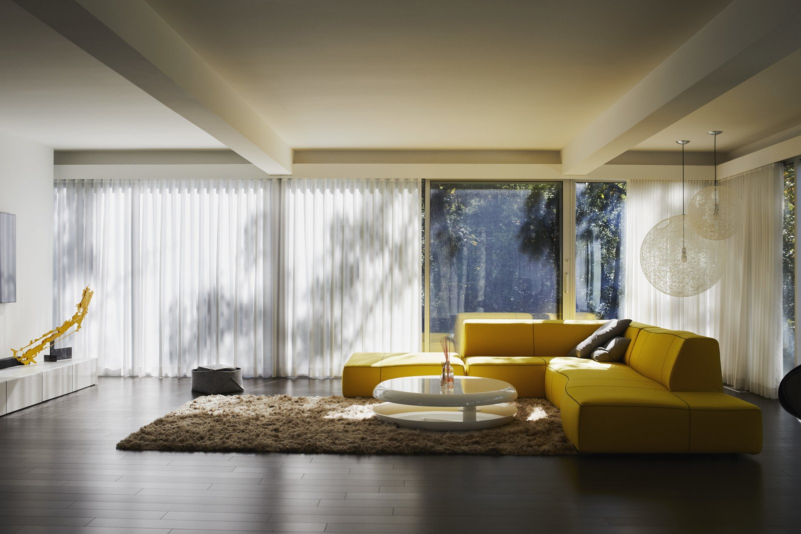 Living Room, Rug Floor, Dark Hardwood Floor, Sofa, Pendant Lighting, and Coffee Tables In keeping with Viks's design, the living room remains on the second floor. A bright yellow artwork by Ken'ichiro Taniguchi complements the Bend Sofa by Patricia Urquiola for B&B Italia. The Random pendant lights are by Bertjan Pot for Moooi, the Yo-Yo coffee table is by Emanuele Zenere, and the Maltino Rug is by Linie Design. The hardwood flooring is from the Admiration line by Mirage.  Photo 6 of 15 in Once Covered in Mold, a Midcentury Gem Outside Chicago Is Reborn