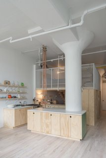 In the kitchen, a quartz Caesarstone countertop hugs the other column.