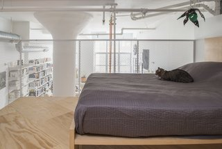 The loft's four-foot-high rail was fabricated by general contractor Create NYC Contracting, using metal mesh from McNichols. The bed is by Nathaniel Wojtalik.