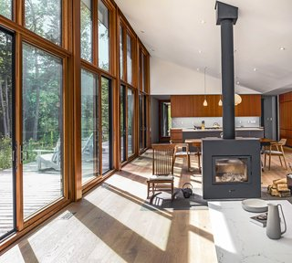 This Home in the Ontario Wilderness Is 12 Miles From the Nearest Powerline - Photo 1 of 7 - Large south-facing windows by Loewen and a high-efficiency Rais X wood-burning stove help to reduce energy demands.