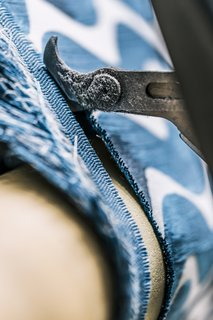 <b>10 Trim the Selvedge</b> As the loom weaves, the fabric continuously advances forward and is rolled onto a beam<br>at the front of the loom. As it rolls out, cutters trim the edges, creating the textile's finished width.