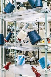"""<b>7 Introduce Color</b> The warp, which is made of thousands of fine yarns, acts as a """"carrier"""" for the blue and off-white cotton weft yarns. The binary file controls how and when the warp threads are manipulated to make way for the weft yarn."""