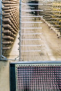 """<b>3 Wind The Warp</b> Before weaving the pattern, weavers at the mill must prepare the warp, which creates the vertical structure of the fabric. Here, a """"creel"""" holds hundreds of cones of yarn that will be used to start building the warp."""