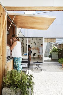 This DIY Home in New Zealand Doubles as a Coffee Spot and Art Gallery - Photo 3 of 16 - Grant built the steel-and-cypress gate. On the other side, he set up his coffee kiosk and art gallery.