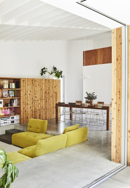 "In the living area, a cedar storage unit made by Grant features a five-by-five-foot sliding panel that conceals shelving and the television. ""It's a way to make it feel less like a TV room during the day,"" Beer says. The sunken sofa—a throwback to the residents' childhoods in the 1970s— is from the Houdini collection by King Living. The dining chairs were a secondhand purchase."