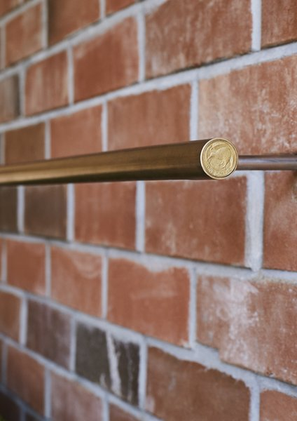 <b>Door Pulls & Lights:</b> Grant made many of the light fixtures and door pulls himself using brass tubing. For the lights, he realized that a New Zealand dollar coin was the perfect size for the end caps, a discovery that saved him $36 on store-bought versions.
