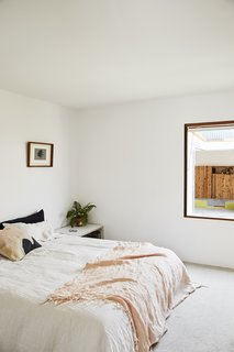 This DIY Home in New Zealand Doubles as a Coffee Spot and Art Gallery - Photo 8 of 16 - Grant painted the master bedroom and the rest of the interior Alabaster by Resene. For big jobs, like framing the walls, they relied on Langsford Construction.