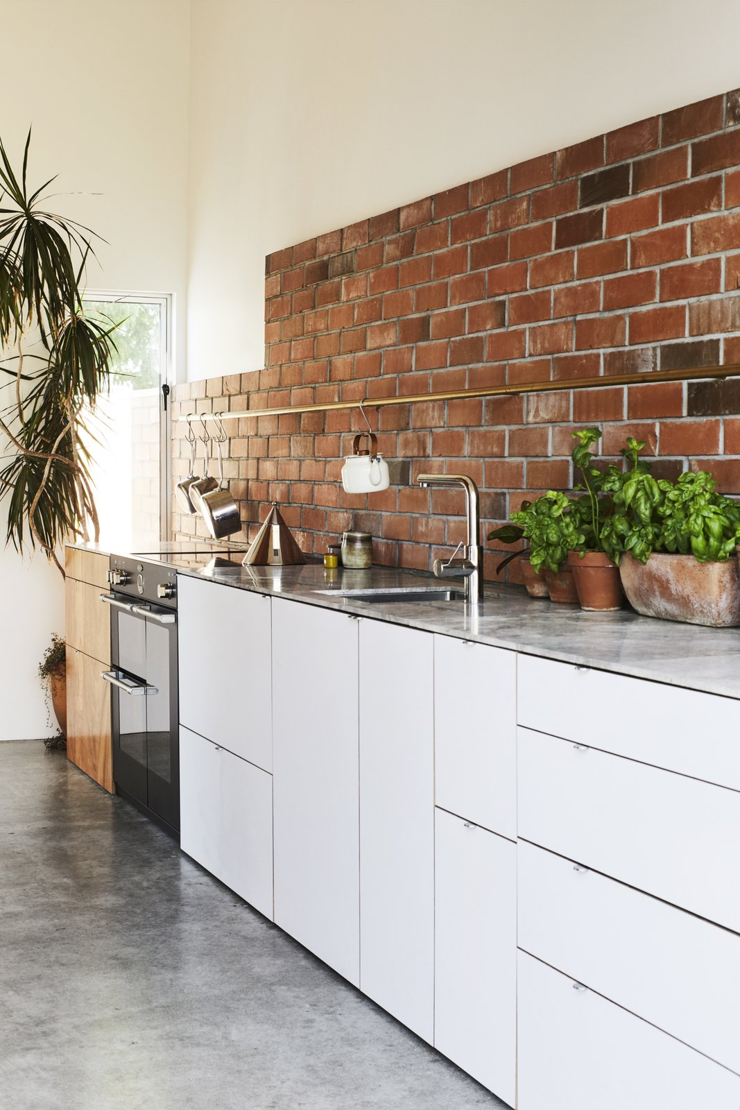 Kitchen, White, Brick, Wall Oven, Concrete, Undermount, and Marble  Kitchen Undermount Wall Oven Marble Brick Photos from This DIY Home in New Zealand Doubles as a Coffee Spot and Art Gallery
