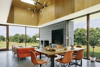 Two Designers Create a Small but Luxe Retreat in the Catskills - Photo 3 of 8 - Polished concrete blocks and a concrete floor are contrasted by a birch plywood tray ceiling. Paola and Jason cut the vertical strips in the ceiling themselves and placed fabric behind to soften the acoustics. Custom brackets were added to the modular seating from West Elm, the table top and legs were found on Etsy, and the chandelier is by Avenue Lighting.