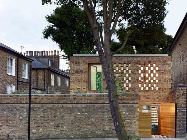 """""""Funton Old Chelsea Yellow brick with a Flemish-like bond is used to directly pick up on the existing predominant brick style of the older neighboring houses,"""" say the architects. A modest entry courtyard with a tiled floor is tucked just behind the front gate."""