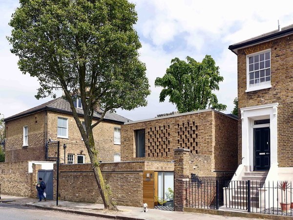 A Perforated Brick Facade Shields a Glowing London Infill Home