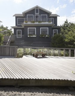 Three-quarters of a century after it was built, a beach home in Saltaire, New York, was elevated eight feet and enlarged by adding a new second story. Its cedar shingles were coated in Benjamin Moore's Westcott Navy 1624.