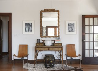 Owner Michael Silber introduced an eclectic mix of furniture with help from interior designer Tracey Garet. By the front door, an antique mirror hangs over a rattan desk; the leather T chairs are by Katavolos, Littell & Kelley.