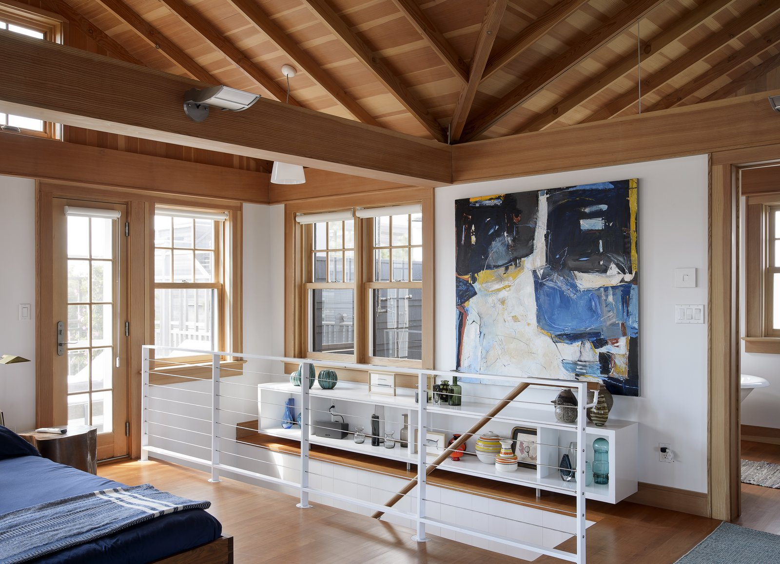 """A vintage red Italian pendant hangs overhead. The painting at the top of the stairs is by Barbara Johnson. """"Having paintings in the house gives a wonderful sense of fantasy,"""" says Michael. """"They enrich the house without competing with the beach."""""""