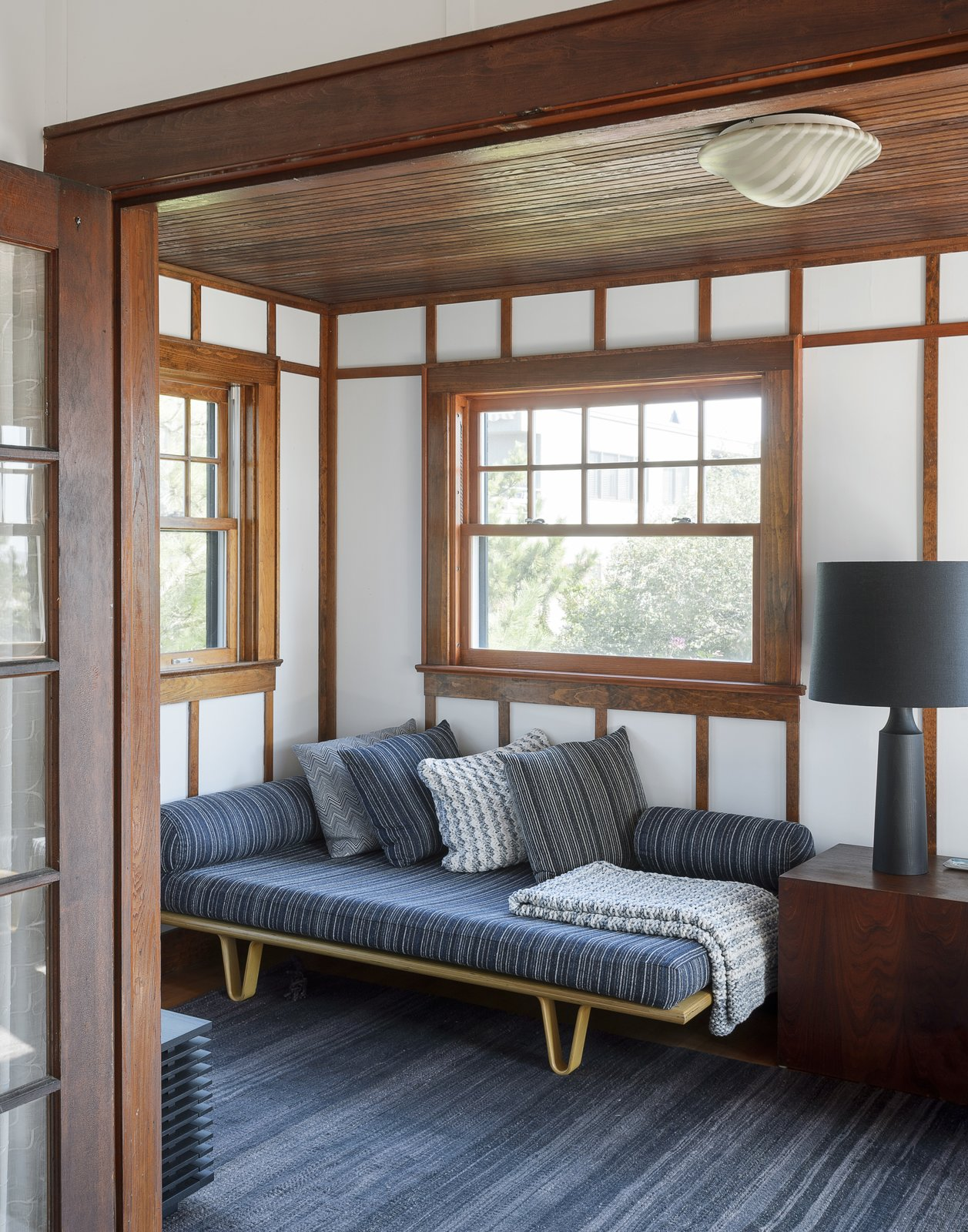 Living Room, Ceiling Lighting, Sofa, Table Lighting, Rug Floor, End Tables, and Dark Hardwood Floor  Best Photos from This Eclectic Beach Bungalow on Fire Island Was Saved After Sandy