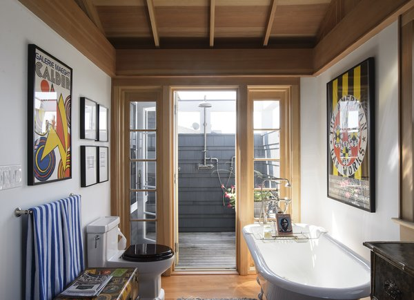 Bath Room, Medium Hardwood Floor, Freestanding Tub, Rug Floor, and One Piece Toilet  Best Photos from This Eclectic Beach Bungalow on Fire Island Was Saved After Sandy