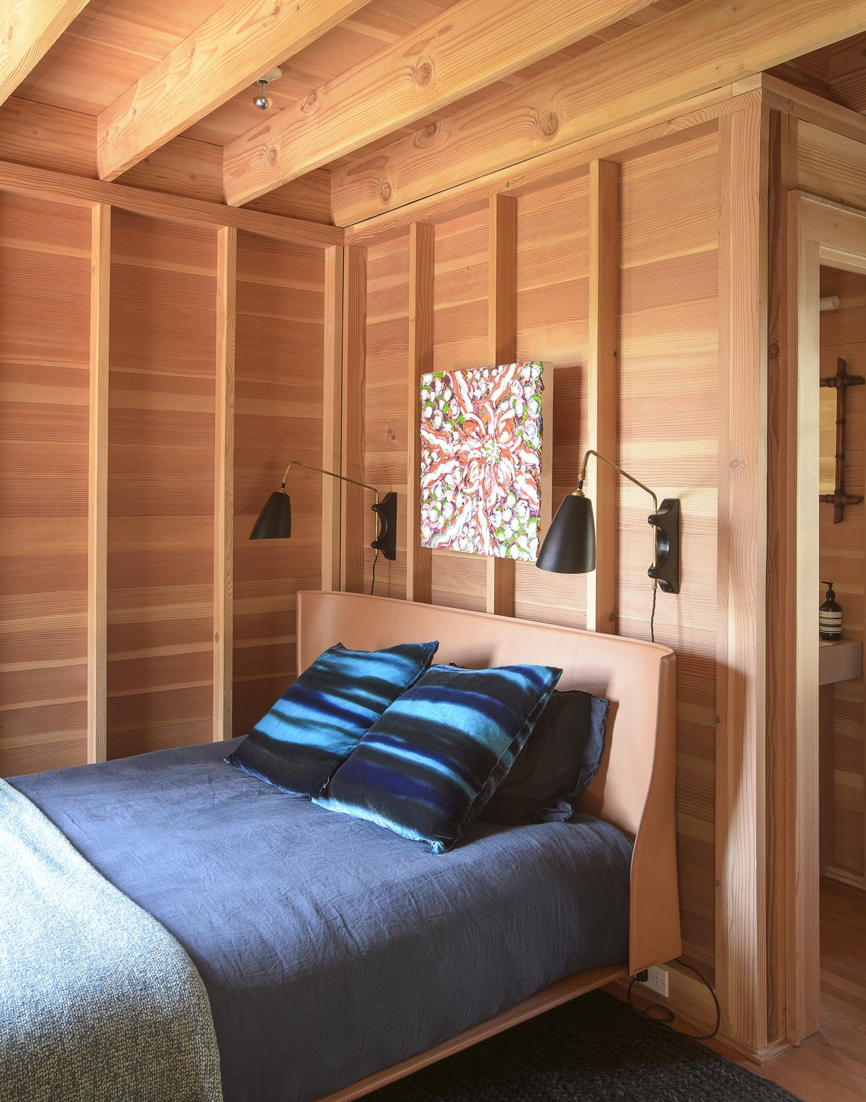 Bedroom, Rug Floor, Bed, Wall Lighting, and Medium Hardwood Floor  Best Photos from This Eclectic Beach Bungalow on Fire Island Was Saved After Sandy