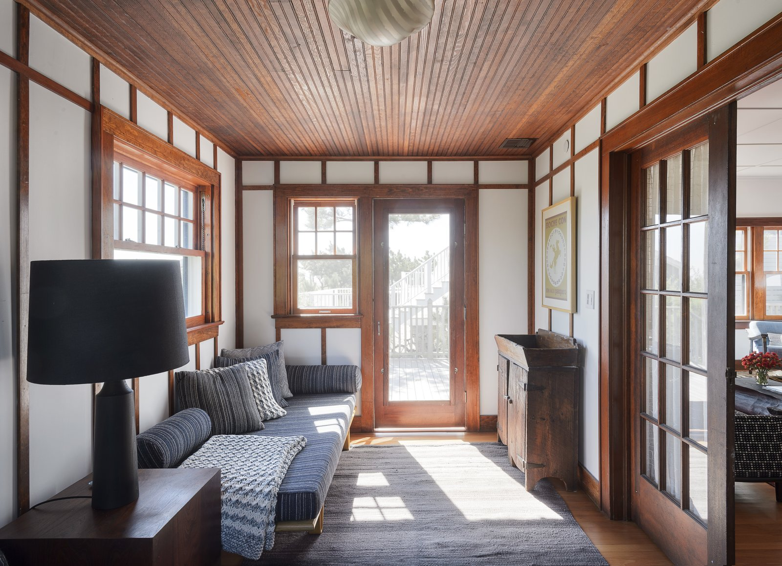 Living Room, End Tables, Rug Floor, Sofa, Table Lighting, Ceiling Lighting, Lamps, and Medium Hardwood Floor  Best Photos from This Eclectic Beach Bungalow on Fire Island Was Saved After Sandy