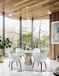 Because the property slopes to the rear, the home's eastern view is of treetops right outside. In the dining nook, Executive Armchairs by Eero Saarinen join a Warren Platner table beneath a Serge Mouille ceiling light. A patterned rug by AVO rests on the terrazzo tile floor.