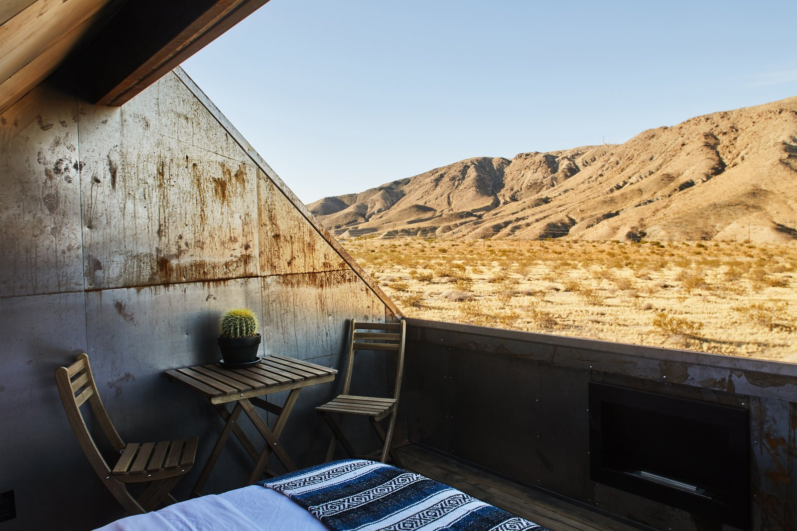 Outdoor, Desert, and Wood Patio, Porch, Deck Alqadi topped the second cabin, which houses a water tank and the site's mechanicals, with a north-facing deck for sunbathing and sleeping under the stars. In addition to a heated bed, it includes a bio-ethanol fireplace and a projector for watching movies on the back wall. A custom cover fits over the opening when rain is expected.  Photo 5 of 13 in These Tiny, Off-the-Grid Cabins Near Joshua Tree Look Totally Apocalypse-Proof