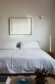 A scalloped bench by Alma Allen rests at the foot of the bed in the master bedroom.