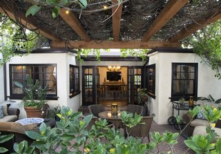 Determined to keep the courtyard—and its striking, verdant baldachin—a focal point of the home, the homeowners went to great lengths to protect the trumpet vines while updating the pergola with a more resilient material.