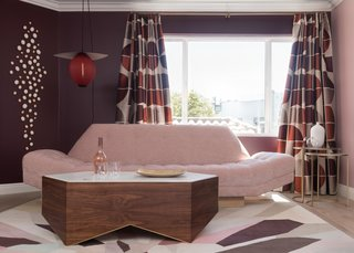 "Designer Melanie Coddington of Coddington Design tranformed the family room into her ""Unapologetically Pink Rosé Lounge."" Inspired by edginess and fueled by French rosé wine, the lounge is modern, opulent, and without a doubt, unapologetically pink. The lounge revolves around a geometric marble and walnut cocktail table with brass inlaid rings to mimic wine stains. Nearby sits a midcentury-style gondola sofa with custom fabric and a classic American 1950s swivel chair."