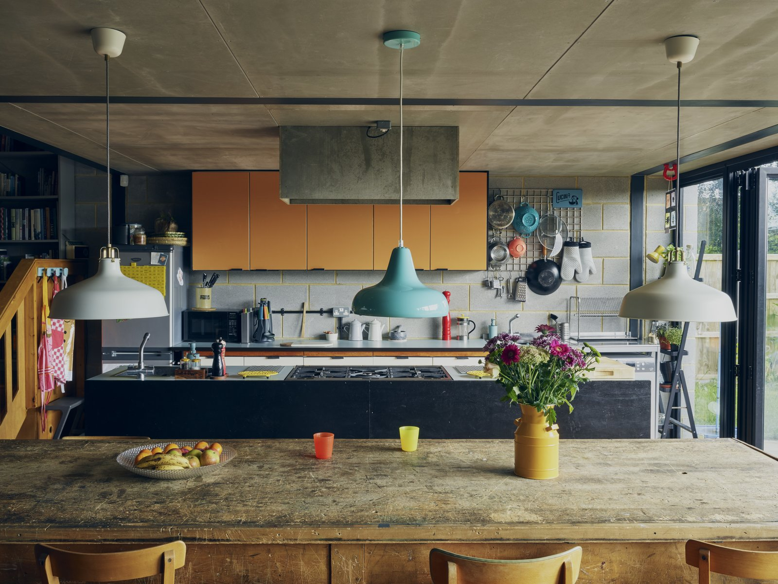 The kitchen is now part of the large open living space. The 1960s Hygena formica cabinets in Polyester Pumpkin were a vintage find. The white pendants are from IKEA and the blue is from Habitat.