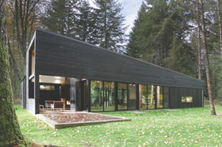 Architect Robert Hutchinson suggested finishing the Western Red Cedar siding of this home with a black semi-transparent stain, and the homeowners were originally skeptical. But they ended up loving it.