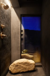 A large boulder from the property provides seating in the shower.