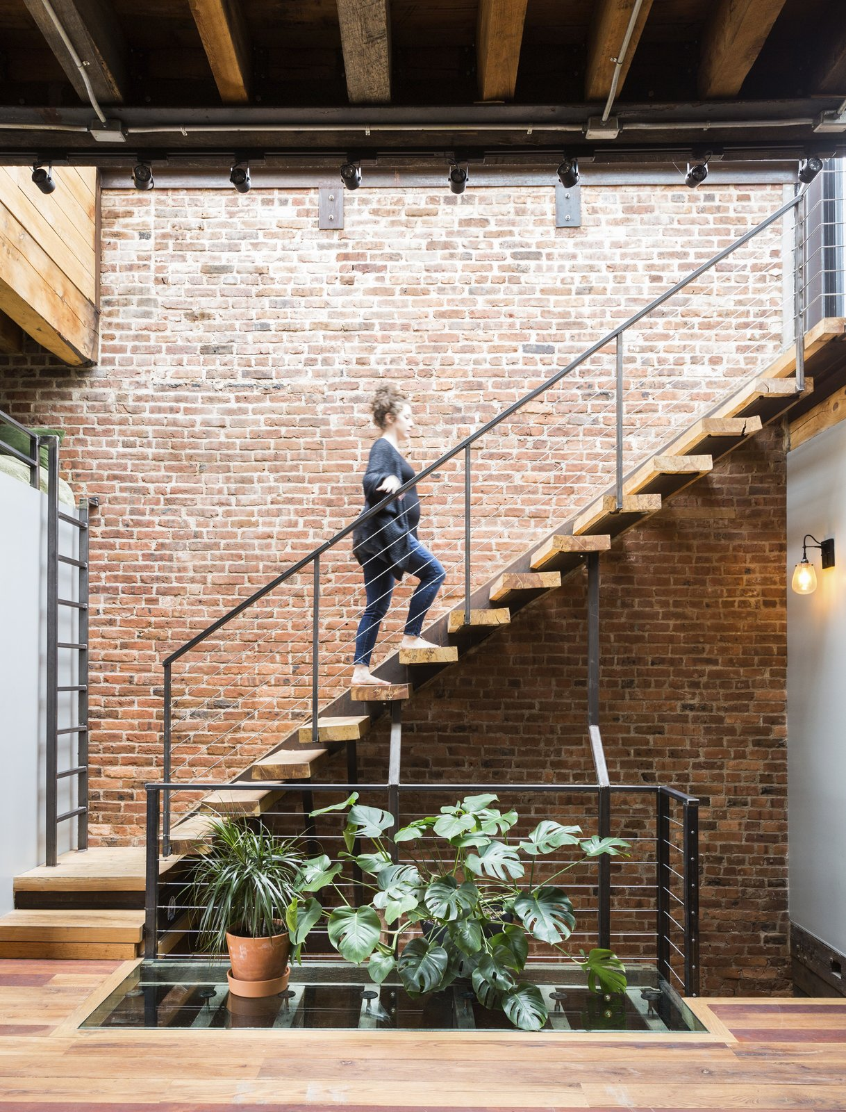 Staircase, Wood Tread, and Metal Railing Next to the steel-and-wood staircase, which leads to the roof, a patch of glass flooring lets sunlight filter down to the bedrooms.  Photo 4 of 5 in In Brooklyn, an 1890s Townhouse Is Reborn With Tons of Light and a Crisp Black Facade