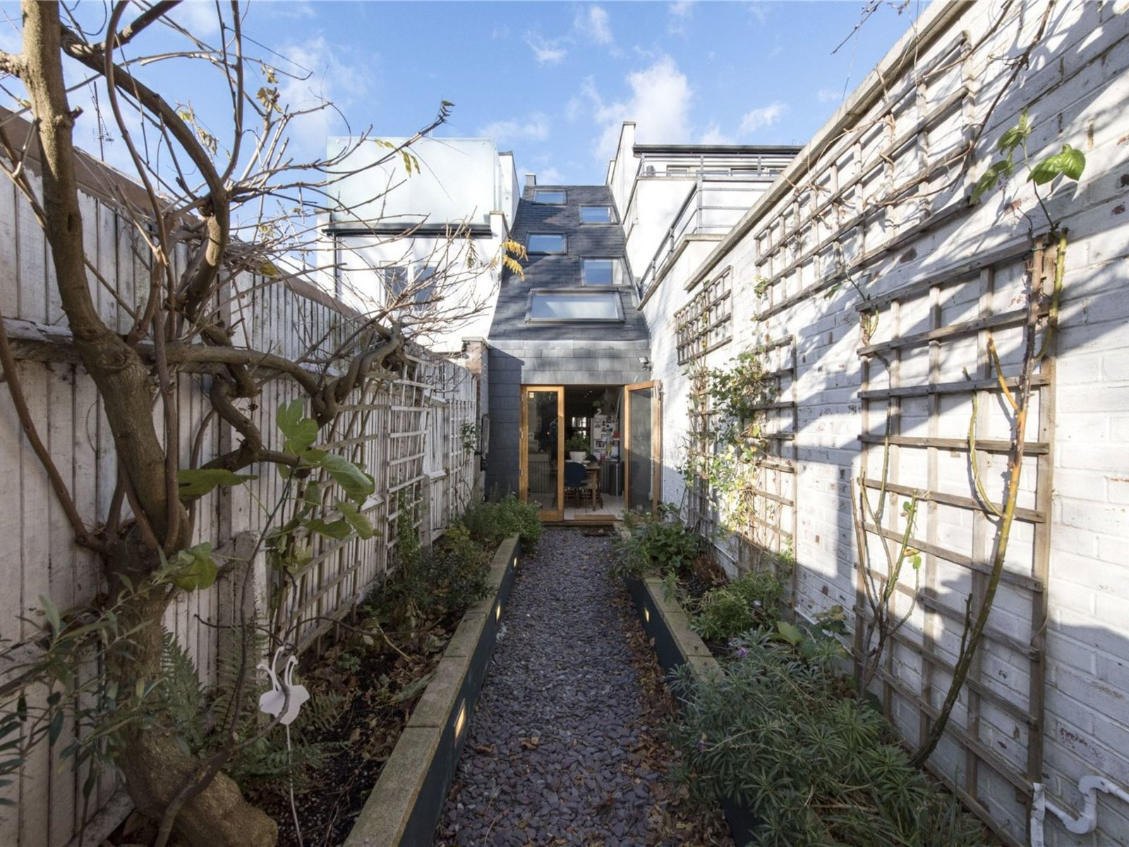 Outdoor, Back Yard, Stone Fences, Wall, Gardens, Wood Fences, Wall, and Garden  Photo 1 of 11 in A Super Skinny London Home Hits the Market at £1M