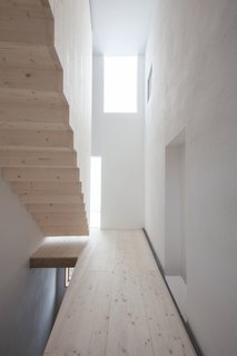 The floating spruce staircase is housed in a new tower-like volume.