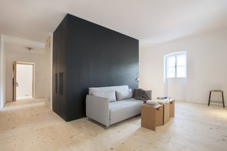 The second-floor vacation suite has a convertible Softline sofa and cardboard stools from Strange Design. The storage unit is clad in black MDF.