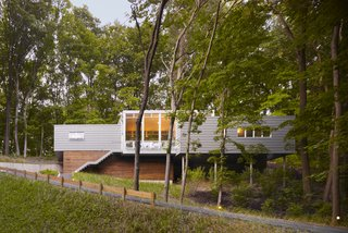 The house, which sits on a long, skinny footprint hugging the dune's steep slope, is made up of three separate sections—two sleeping spaces connected in the middle by a living space.