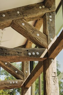 Working with Lancaster County Timber Frames and engineer John Schneider, the architects repurposed aged oak beams for the extensions; the new metal fasteners were painted white.