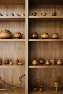 Walnut shelving showcases an extensive collection of treens by 19th-century Ohio woodworker David Mills Pease.